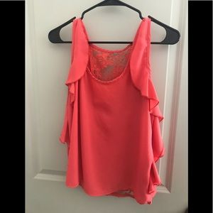 Sleeveless coral blouse.